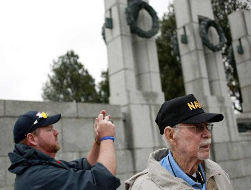 Spencer Keepers (left) takes pictures while his father Vernon Keepers looks at the National WWII Memorial in Washington D.C. on Wednesday, Oct. 12, 2011. Veterans from Oklahoma visited the National WWII Memorial during an Oklahoma Honor Flight to Virginia and Washington D.C. Photo by John Clanton, The Oklahoman ORG XMIT: KOD