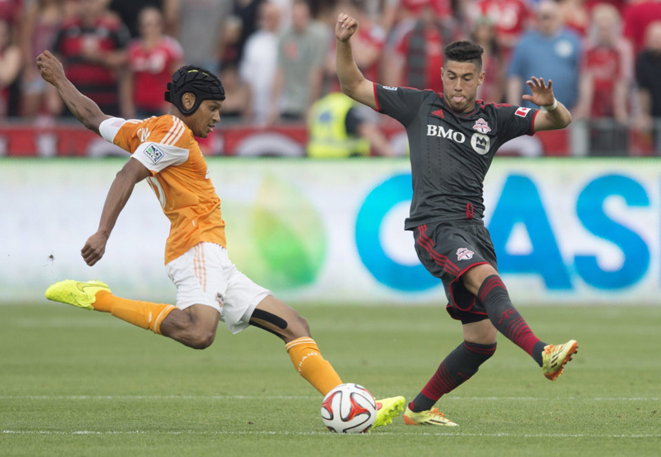 Photo - Houston Dynamo's Ricardo Clark, left, takes a shot in front of Toronto FC's Jonathan Osorio during the first half of a soccer game, Saturday, July 12, 2014 in Toronto. (AP Photo/The Canadian Press, Darren Calabrese)