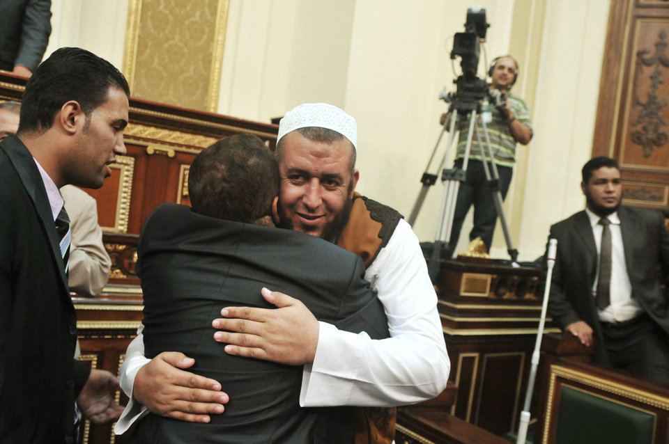 Egyptian members of parliament hug each other at the Parliament in Cairo, Egypt, Tuesday, July 10, 2012. Egypt's Islamist-dominated parliament opened a new front in the country's leadership showdowns Tuesday by meeting in defiance of orders that disbanded the chamber and brought President Mohammed Morsi in conflict with both the powerful military and the highest court. (AP Photo) ORG XMIT: CAI110