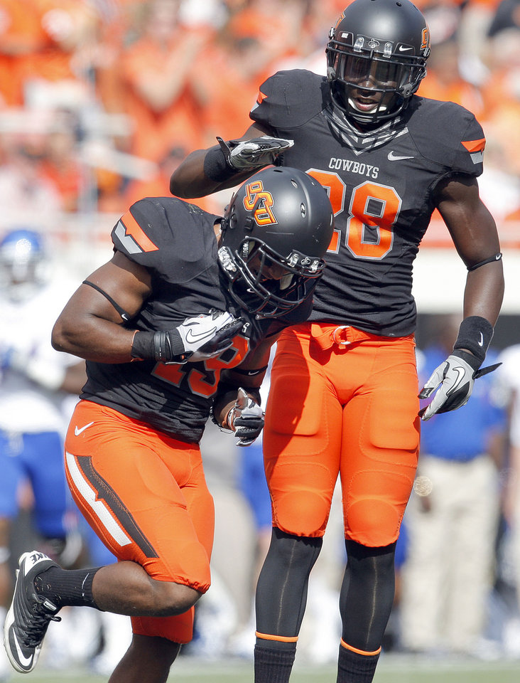 Photo - Oklahoma State's Brodrick Brown (19) and Deion Imade (28) celebrate a sack during the first half of the college football game between the Oklahoma State University Cowboys (OSU) and the University of Kansas Jayhawks (KU) at Boone Pickens Stadium in Stillwater, Okla., Saturday, Oct. 8, 2011. Photo by Sarah Phipps, The Oklahoman