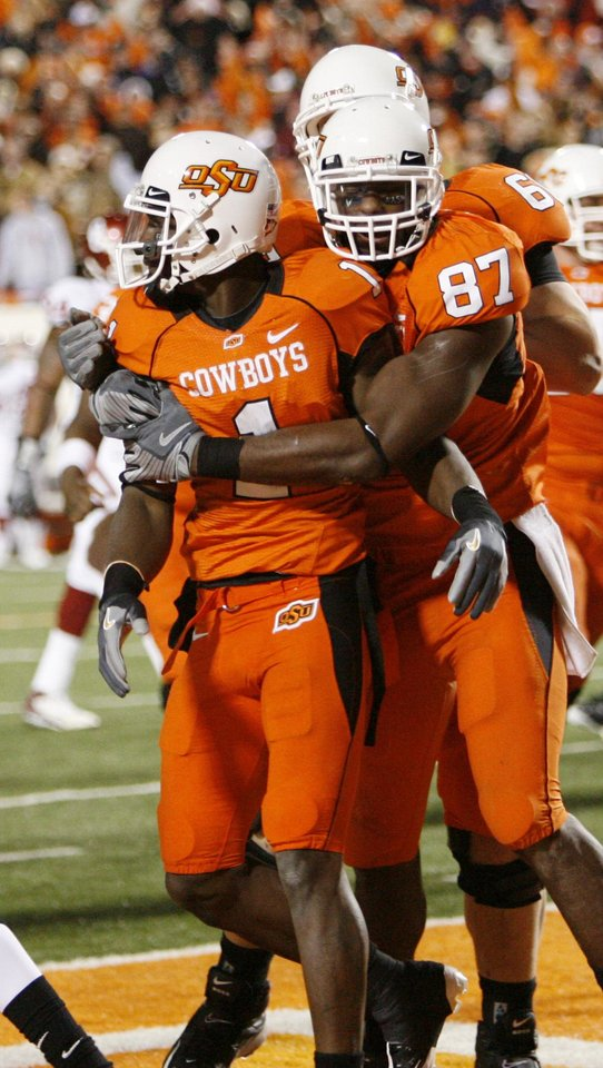 Brandon Pettigrew hugs Dez Bryant after TD catch by Bryant during the second half of the college football game between the University of Oklahoma Sooners (OU) and Oklahoma State University Cowboys (OSU) at Boone Pickens Stadium on Saturday, Nov. 29, 2008, in Stillwater, Okla. STAFF PHOTO BY NATE BILLINGS