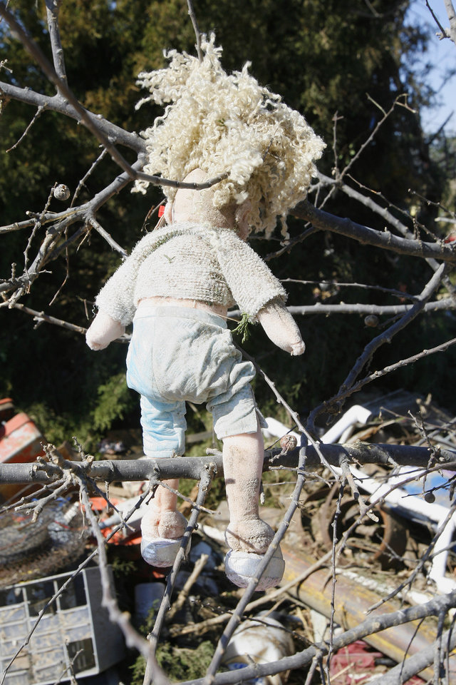 Photo - A child's doll hangs in a tree with other debris from a mobile home on Brock Road in Lone Grove, Wednesday, Feb. 11, 2009. BY PAUL B. SOUTHERLAND, THE OKLAHOMAN