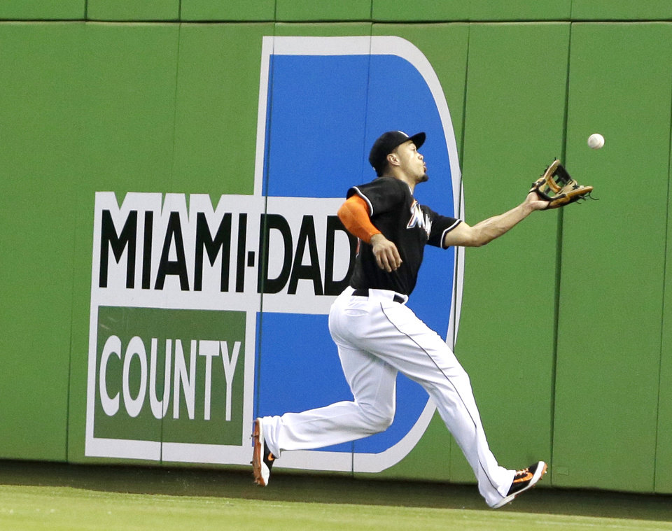 Photo - Miami Marlins right fielder Giancarlo Stanton catches a foul ball hit by Oakland Athletics' Josh Donaldson during the first inning of a baseball game, Saturday, June 28, 2014 in Miami. (AP Photo/Wilfredo Lee)