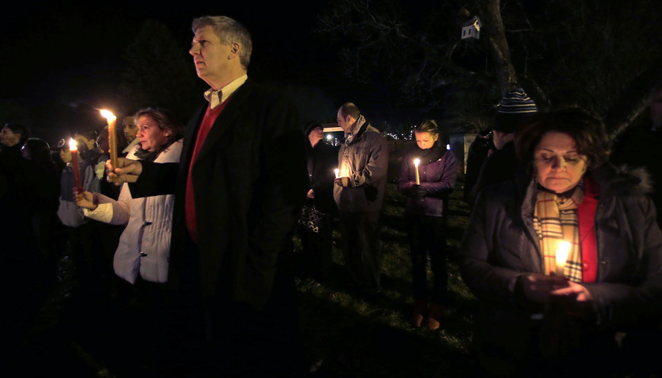 Photo - Men and women hold candles in vigil outside St. Rose of Lima Roman Catholic Church during a healing service held in for victims of an elementary school shooting in Newtown, Conn., Friday, Dec. 14, 2012.  A gunman opened fire at Sandy Hook Elementary School in the town, killing 26 people, including 20 children. (AP Photo/Charles Krupa)