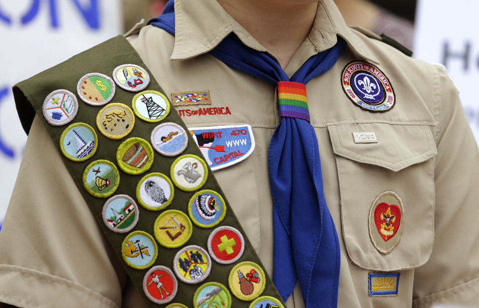 Photo - The Boy Scout uniform of Pascal Tessier, 17, a gay Eagle Scout from Kensington, Md., includes his merit badges and a rainbow-colored neckerchief slider, as he speaks in front of a group of Boy Scouts and scout leaders, Wednesday, May 21, 2014, outside the headquarters of Amazon.com in Seattle. The group delivered a petition to Amazon that was started as an online effort by Tessier and gathered more than 125,000 signatures, urging Amazon to stop donating money to the Boy Scouts due to the organization's policy of excluding openly gay adults from leadership positions, despite recently accepting gay youth as scouts. (AP Photo/Ted S. Warren)
