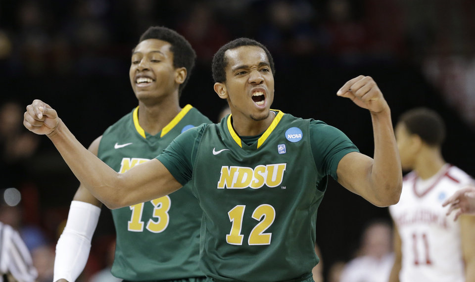Photo - North Dakota State's Lawrence Alexander (12) celebrates in overtime during a second-round game against Oklahoma in the NCAA men's college basketball tournament in Spokane, Wash., Thursday, March 20, 2014. North Dakota State won 80-75. (AP Photo/Elaine Thompson)