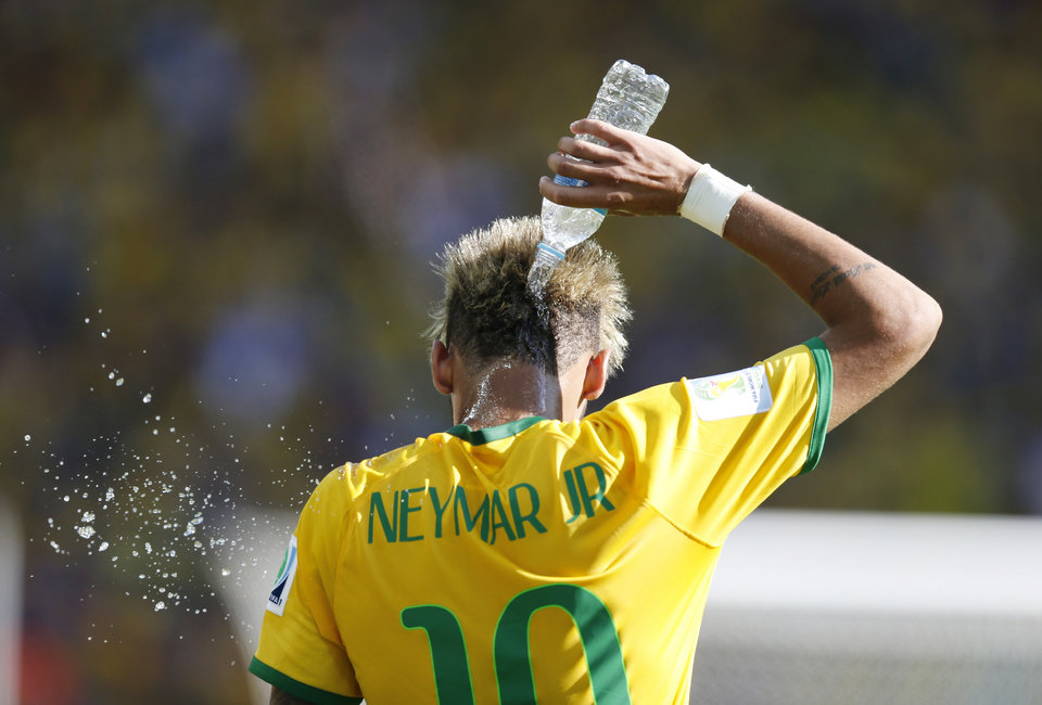 Photo - Brazil's Neymar cools himself up with water during the World Cup round of 16 soccer match between Brazil and Chile at the Mineirao Stadium in Belo Horizonte, Brazil, Saturday, June 28, 2014. (AP Photo/Frank Augstein)