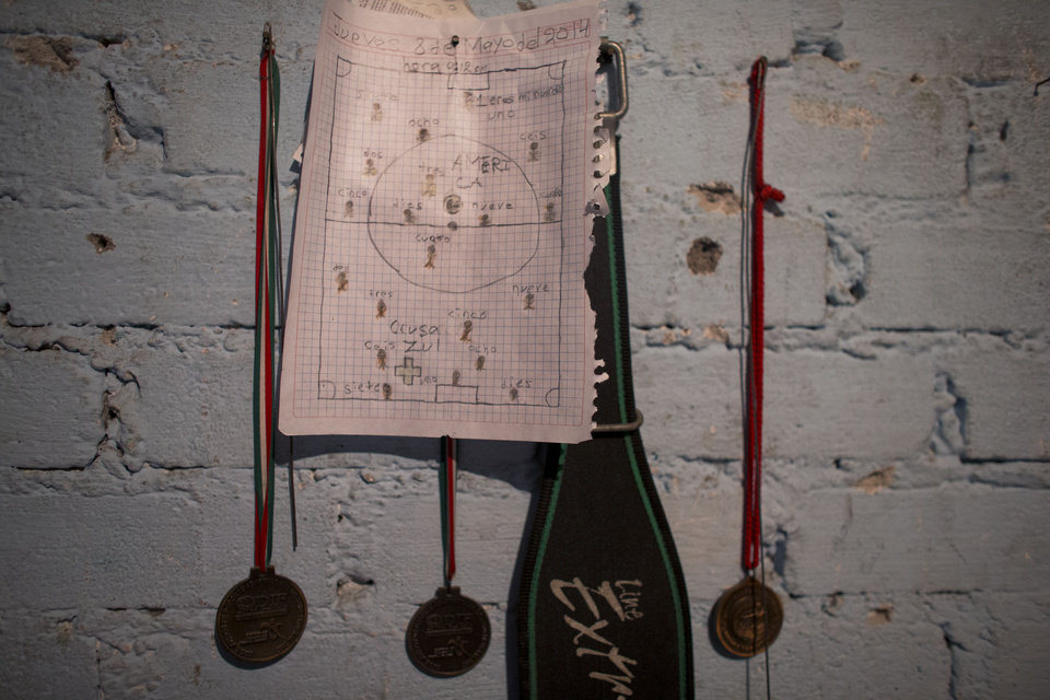 Photo - In this Friday, June 6, 2014 photo, medals for track and field hang on the wall of Miguel Angel Canela's home workshop, along with a matchup of favorite teams made for him by a relative, in the Valle de Chalco area of Estado de Mexico. Canela says he has been an athlete all his life, and losing his sight at age 23 did not stop him.