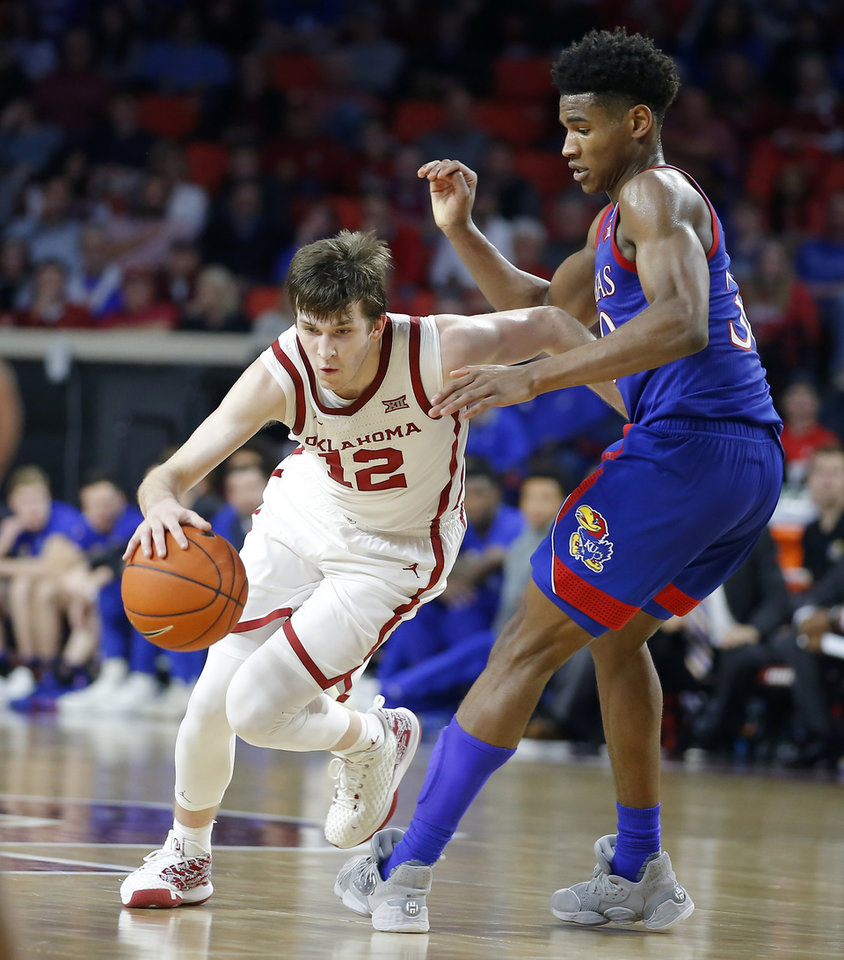 Photo - Oklahoma's Austin Reaves (12) goes past Kansas' Ochai Agbaji (30) during an NCAA college basketball game between the University of Oklahoma Sooners (OU) and the University of Kansas Jayhawks at Lloyd Noble Center in Norman, Okla., Tuesday, Jan. 14, 2020. Oklahoma lost 66-52.  [Bryan Terry/The Oklahoman]