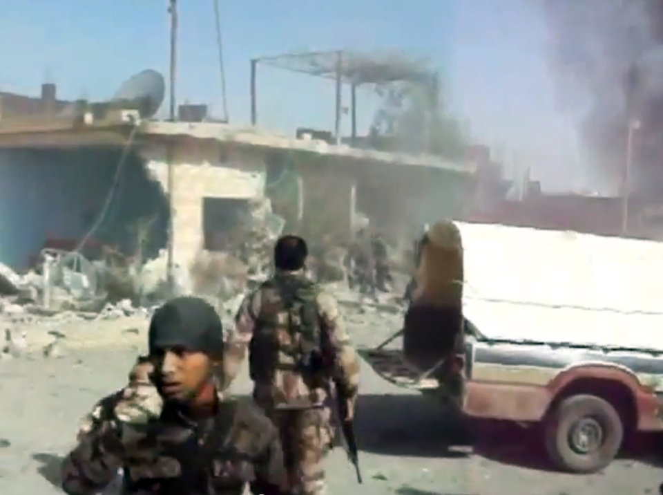 Photo -   This image taken from video obtained from Shaam News Network, which has been authenticated based on its contents and an Associated Press journalist who saw a plane bomb an area around the Syrian-Turkish border town of Ras al-Ayn, shows Syrians rebels inspecting the damage moments after an airstrike by Syrian warplanes in Ras al-Ayn, Syria, Monday, Nov. 12, 2012. (AP Photo/Shaam News Network via AP video)