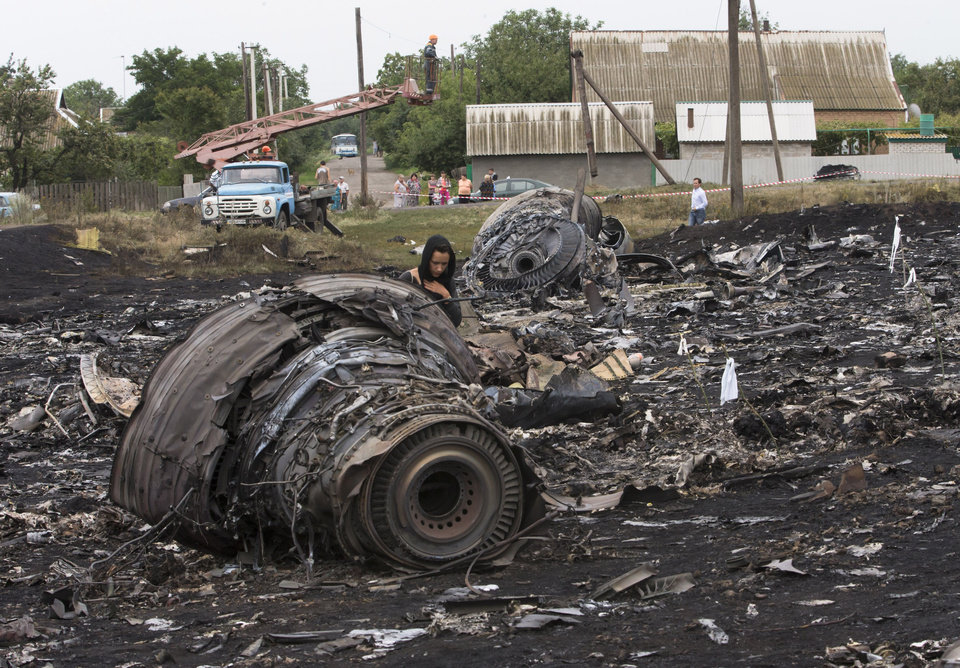 Photo - A woman walks at the site of a crashed Malaysia Airlines passenger plane near the village of Rozsypne, eastern Ukraine Friday, July 18, 2014. Rescue workers, policemen and even off-duty coal miners were combing a sprawling area in eastern Ukraine near the Russian border where the Malaysian plane ended up in burning pieces Thursday, killing all 298 aboard. (AP Photo/Dmitry Lovetsky)