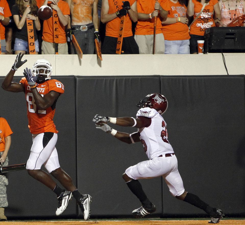 Photo - OSU's Justin Blackmon (81) catches a touchdown pass in front of Troy's Bryan Willis (26) during the college football game between the Oklahoma State University Cowboys (OSU) and the Troy University Trojans at Boone Pickens Stadium in Stillwater, Okla., Saturday, Sept. 11, 2010. Photo by Sarah Phipps, The Oklahoman