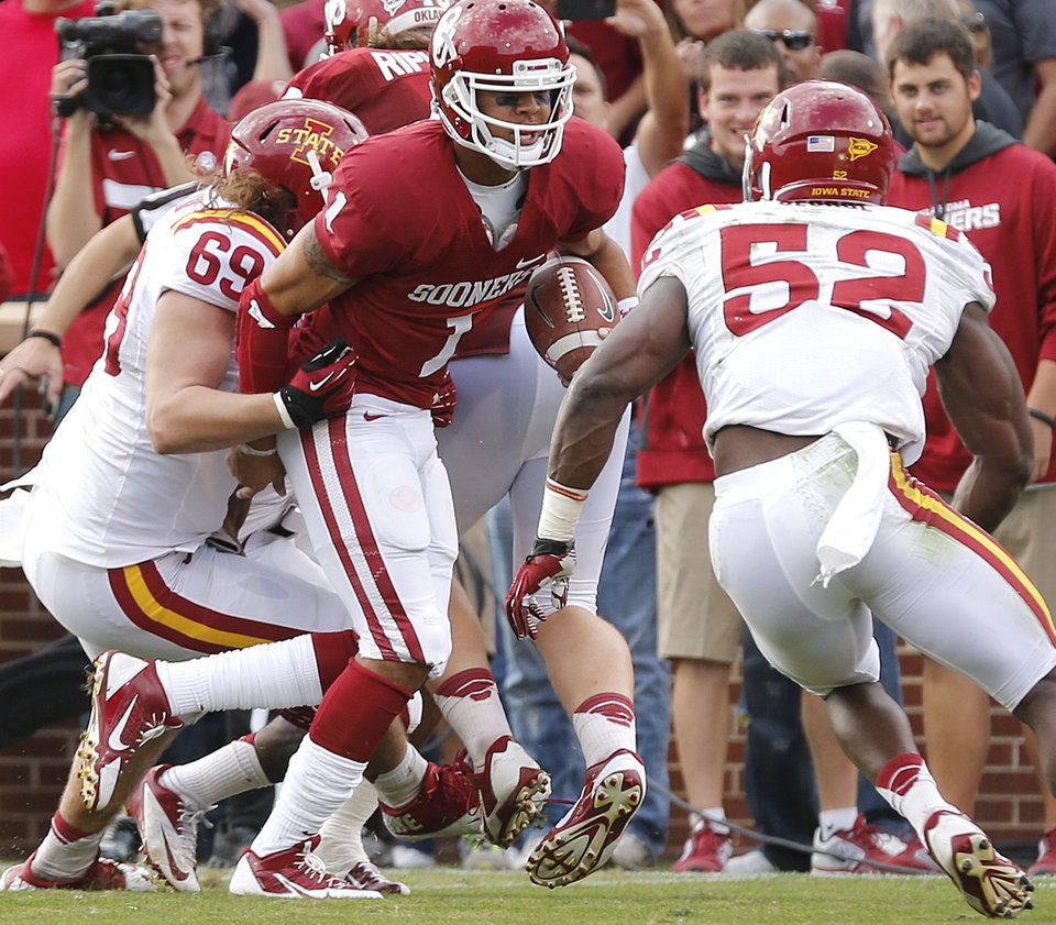 Oklahoma's Kendal Thompson (1) tries to get by Iowa State's Nick Kron (69) and Anthony Lazard (53) during the college football game between the University of Oklahoma Sooners (OU) and the Iowa State University Cyclones (ISU) at Gaylord Family-Oklahoma Memorial Stadium in Norman, Okla. on Saturday, Nov. 16, 2013. Photo by Chris Landsberger, The Oklahoman