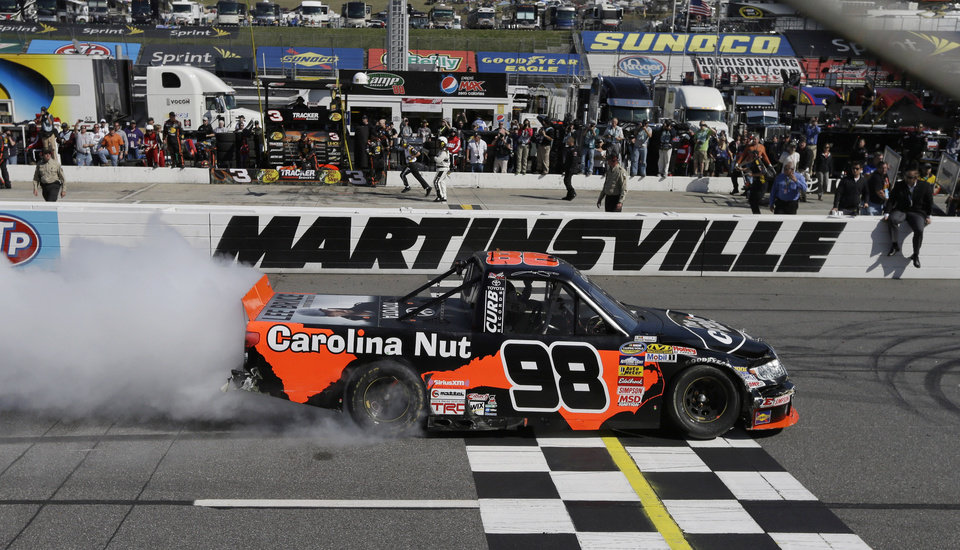 Photo - Driver Johnny Sauter (98) does a burnout as he celebrates winning the Kroger 250 NASCAR Truck series auto race at Martinsville Speedway in Martinsville, Va., Saturday, April 6, 2013. (AP Photo/Steve Helber)