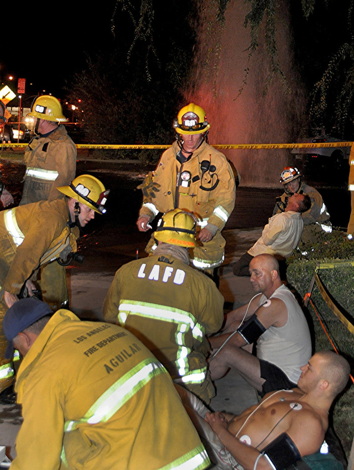 FILE - In this Aug. 22, 2012 file photo, firefighters and paramedics examine two of the eight patients who were shocked after attempting to aid a car crash victim as water gushes from hydrant in the North Hollywood section of Los Angeles. Seven people suffered electric shocks, including two women who were electrocuted, as they rushed to the scene help and were water from the hydrant was electrified by live wires on the utility pole. The driver, Aman Samsonian, has been ordered to stand trial for vehicular manslaughter in the electrocution deaths. (AP Photo/Rick McClure, File)