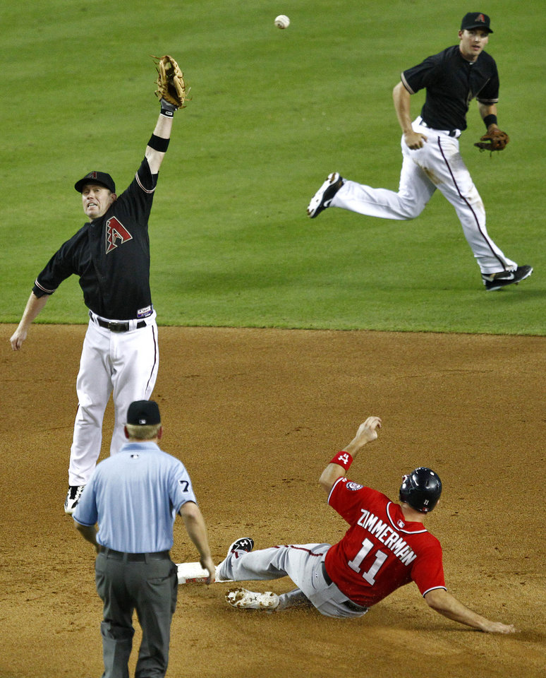Photo -   Washington Nationals' Ryan Zimmerman (11) steals second while Arizona Diamondbacks' Aaron Hill reaches for an overthrown ball as Stephen Drew ,right, backs Hill up during the fifth inning of a baseball game, Saturday, Aug. 11, 2012, in Phoenix. (AP Photo/Matt York)