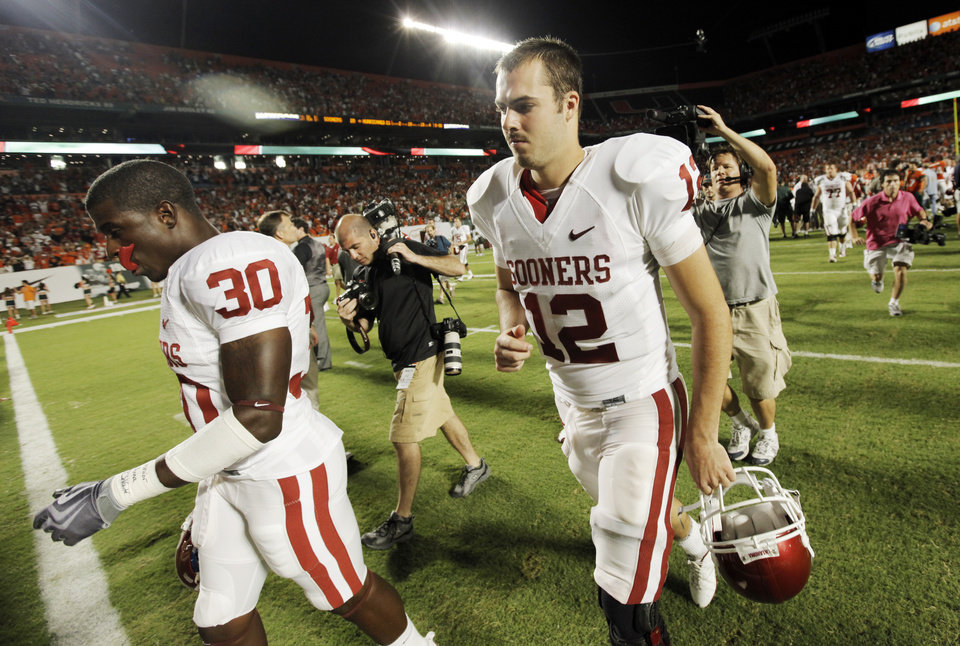 Photo - OU's Landry Jones (12) and Javon Harris (30) leave the field after the college football game between the University of Oklahoma (OU) Sooners and the University of Miami (UM) Hurricanes at Land Shark Stadium in Miami Gardens, Florida, Saturday, October 3, 2009. Miami won, 21-20. Photo by Nate Billings, The Oklahoman