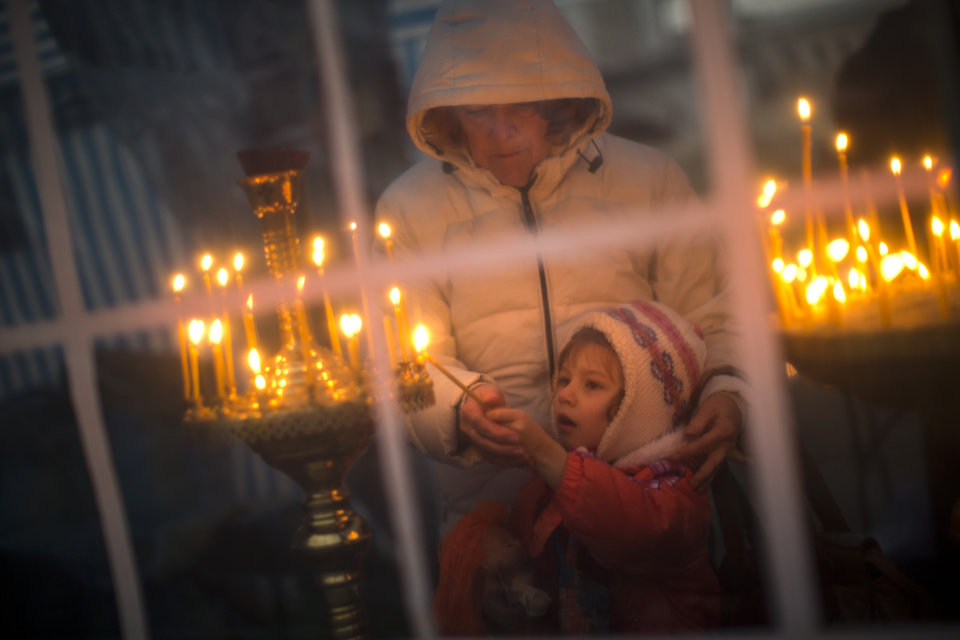 Photo - A boy is helped by his mother to light a candle inside an improvised church at the Independence Square, the epicenter of the country's current unrest, in Kiev, Ukraine, Thursday, Feb. 27, 2014. Ukraine put its police on high alert after dozens of armed pro-Russia men stormed and seized local government buildings in Ukraine's Crimea region early Thursday and raised a Russian flag over a barricade. (AP Photo/Emilio Morenatti)