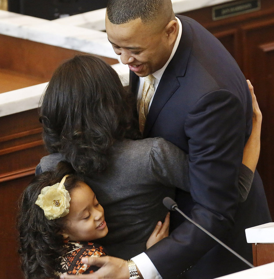 T. W. Shannon is hugged by his wife, Devon, as their daughter, Audrey Grace, joins in the group hug after Shannon took the oath of office when he was elected by his colleagues in the Oklahoma House of Representatives as their Speaker for the upcoming legislative session. Shannon, a Republican from Lawton, is Oklahoma's first black Speaker of the House. He was sworn in on the floor of the House by Oklahoma Supreme Court Chief Justice Tom Colbert on Tuesday, Jan. 8, 2013.  Colbert became  Oklahoma's first black chief justice when he was sworn in last week.    Photo by Jim Beckel, The Oklahoman