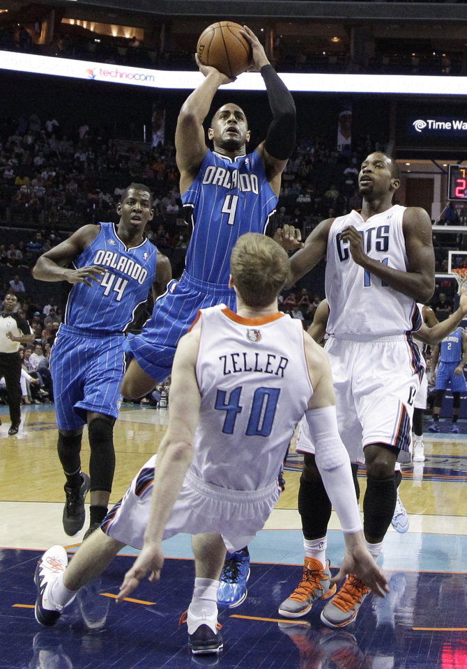 Photo - Orlando Magic's Arron Afflalo (4) runs into Charlotte Bobcats' Cody Zeller (40) during the first half of an NBA basketball game in Charlotte, N.C., Friday, April 4, 2014. Afflalo was called for a charging foul on the play. (AP Photo/Chuck Burton)