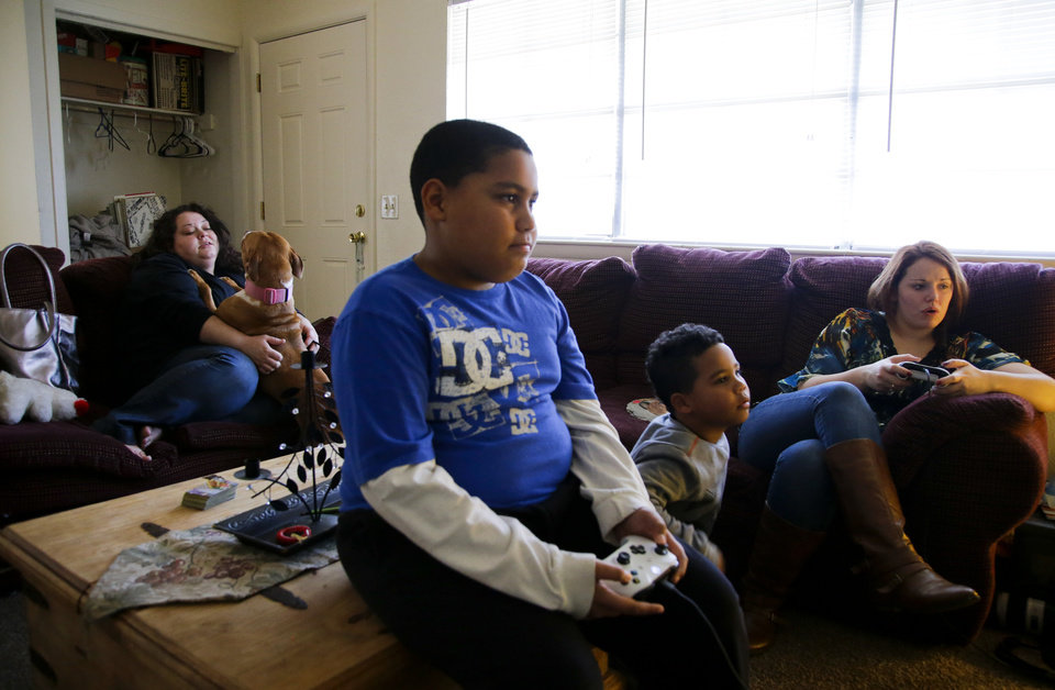 Photo -  Desha Bailey plays with her pit bull terrier Jordan as her sons, Jakobie Roberson, center, 10, and Isaiah Roberson, 6, play the video game