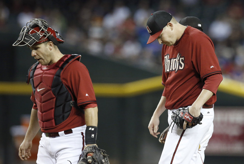 Photo - Arizona Diamondbacks' Trevor Cahill, right, looks down after getting a visit from catcher Miguel Montero after Cahill gave up a run to the Chicago Cubs in the fourth inning of a spring training baseball game, Friday, March 28, 2014, in Phoenix. (AP Photo/Ross D. Franklin)