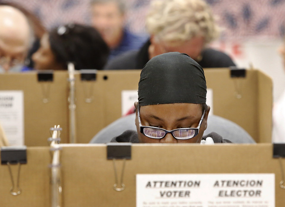A woman studies her ballot at a voting station with other early voters inside the Oklahoma County Election Board on N. Lincoln Blvd,  Monday afternoon, Nov. 5, 2012.    Photo by Jim Beckel, The Oklahoman
