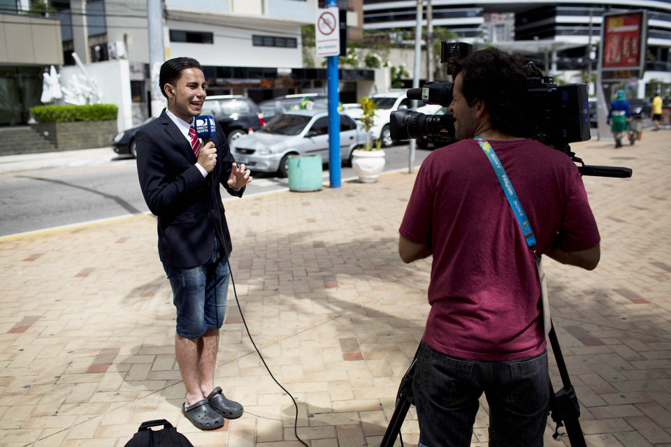 Photo - A Colombian TV reporter works in front of the hotel where the Colombian national soccer team is staying, in Fortaleza, Brazil, Thursday, July 3, 2014. Colombian supporters are in Fortaleza hoping to see some history being made in this northeastern World Cup city where Brazil and Colombia face off in the World Cup quarterfinals, Saturday. (AP Photo/Rodrigo Abd)