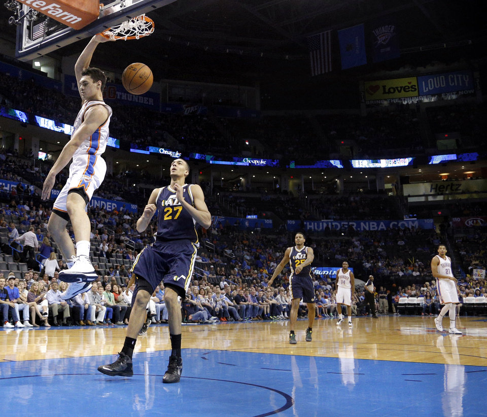 Photo - Oklahoma City 's Steven Adams (12) dunks in front of Utah's Rudy Gobert (27) during the NBA game between the Oklahoma City Thunder and the Utah Jazz at the Chesapeake Energy Arena, Sunday, March 30, 2014, in Oklahoma City. Photo by Sarah Phipps, The Oklahoman