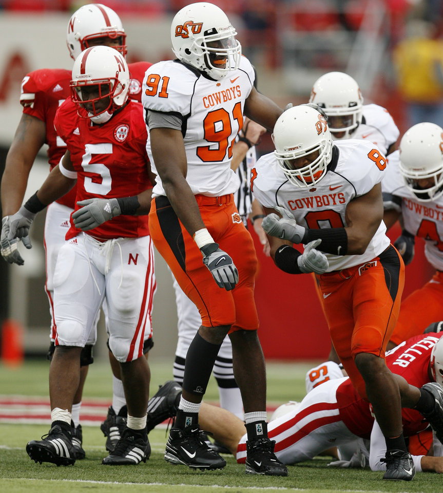 Photo - Donovon Woods, right, and Ugo Chinasa of OSU celebrate in front of Marlon Lucky of Nebraska after a fumble during  the college football game between Oklahoma State University (OSU) and the University of Nebraska at Memorial Stadium in Lincoln, Neb., on Saturday, Oct. 13, 2007. By Bryan Terry, The Oklahoman