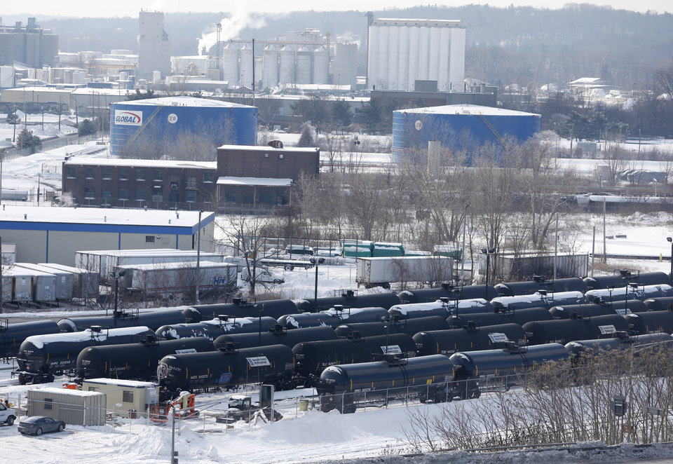 Photo - A view from a nearby apartment building shows vehicles driving along Interstate 787 past railroad oil tanker cars that are lined up at Global Partners at the Port of Albany on Friday, Feb. 7, 2014, in Albany, N.Y. The Port of Albany has become a hub for the U.S. oil business, taking shipments from North Dakota's Bakken Shale daily by mile-long trains and shipping it in tankers down the Hudson River to refineries. Opponents of a proposal to build boilers to liquefy heavy crude passing through Albany by rail are drawing attention to the capital's emergence as a major hub for the transport of oil that's widely considered risky from an environmental and safety standpoint.  (AP Photo/Mike Groll)