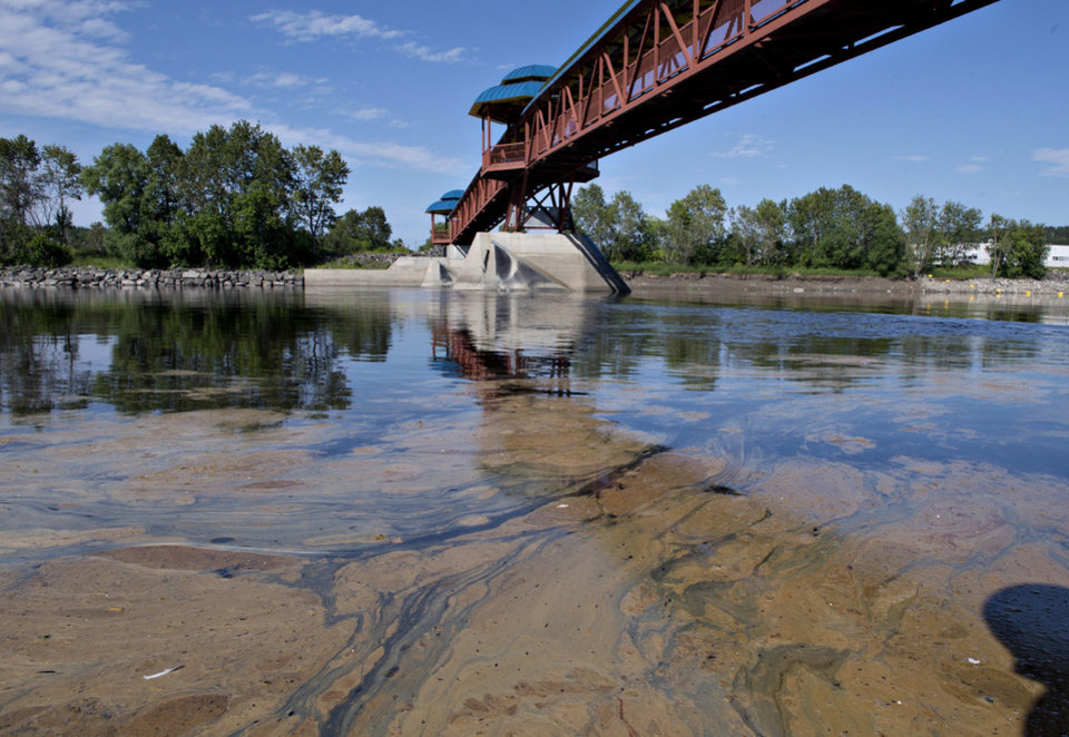 Photo - Traces of the oil spill that occurred following the runaway train derailment Saturfday in Lac-Megantic, Quebec, is seen about 46 miles (70 kilometres)   downstream under a pedestrian bridge in the Chaudiere River at Saint-Georges, Quebec, on Monday, July 8, 2013.   When the train derailed tanker cars filled with oil exploded and destroyed about 30 buildings, including a public library and a popular bar that was filled with revelers.    (AP Photo/ THE CANADIAN PRESS, Jacques Boissinot)