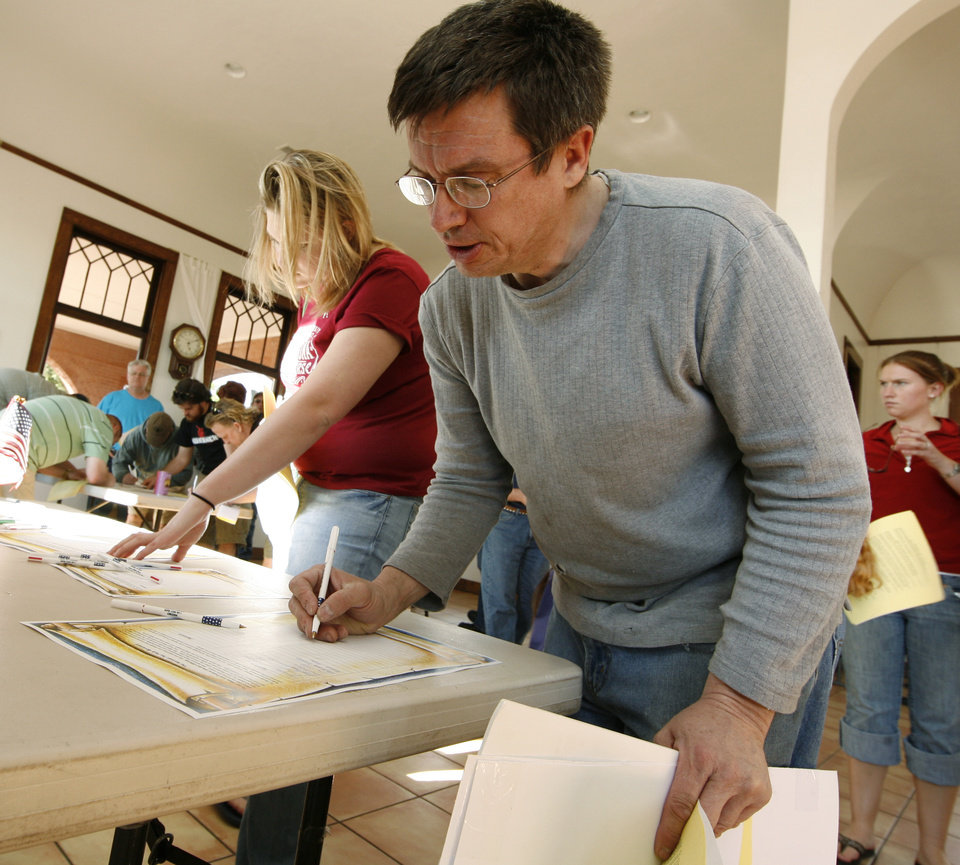 Photo - Mark Woodhouse of Norman joins others in signing a petition as citizens hold a Tax Day Tea Party at the Santa Fe Station in Norman, Okla. on Wednesday, April 15, 2009.  