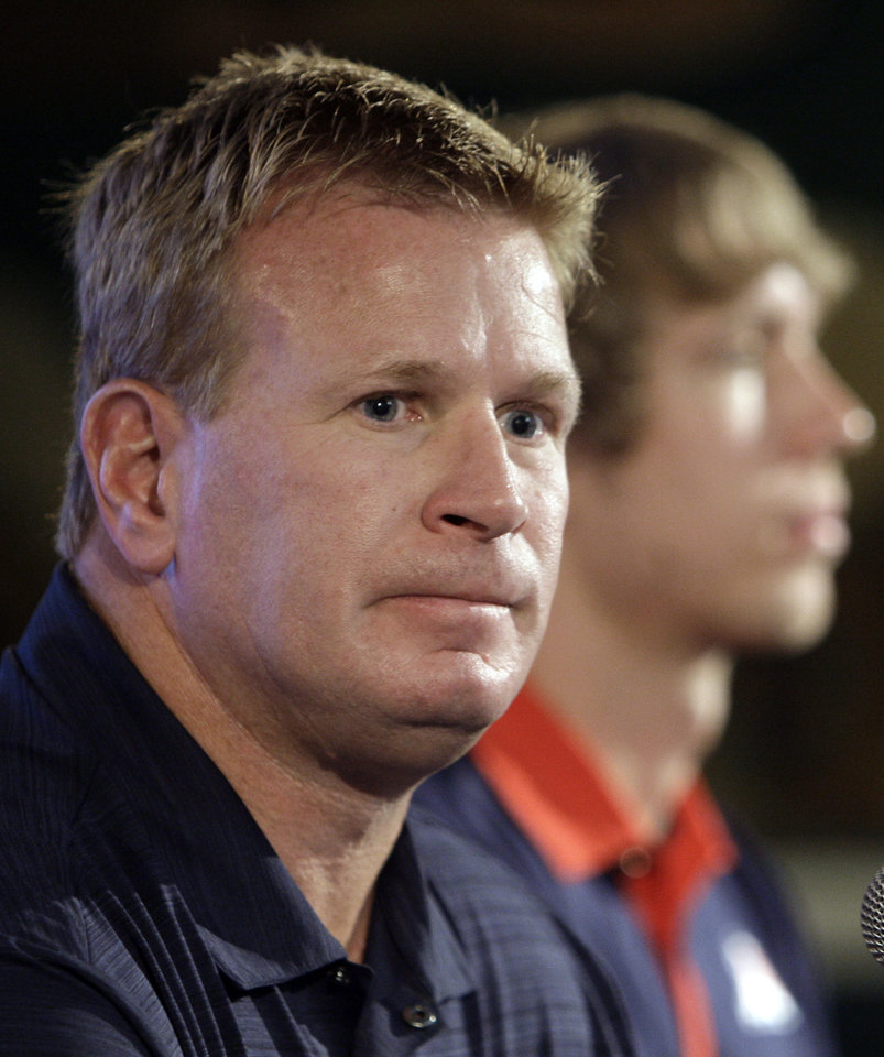 Photo - In this July 26, 2011 photo, Arizona coach Mike Stoops, with quarterback Nick Foles in the background, talks to reporters at the Pac-12 football media day in Los Angeles.  Stoops has been fired halfway through his eighth season at Arizona, athletic director Greg Byrne announced Monday, Oct. 10, 2011. Stoops' dismissal came two days after the Wildcats lost their fifth straight game, 37-27, at previously winless Oregon State. (AP Photo/Reed Saxon) ORG XMIT: CARS901
