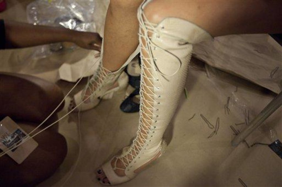 A model has her shoe tied before the Skaist Taylor Spring 2013 collection is modeled during Fashion Week, Sunday, Sept. 9, 2012, in New York. (AP Photo/Karly Domb Sadof)