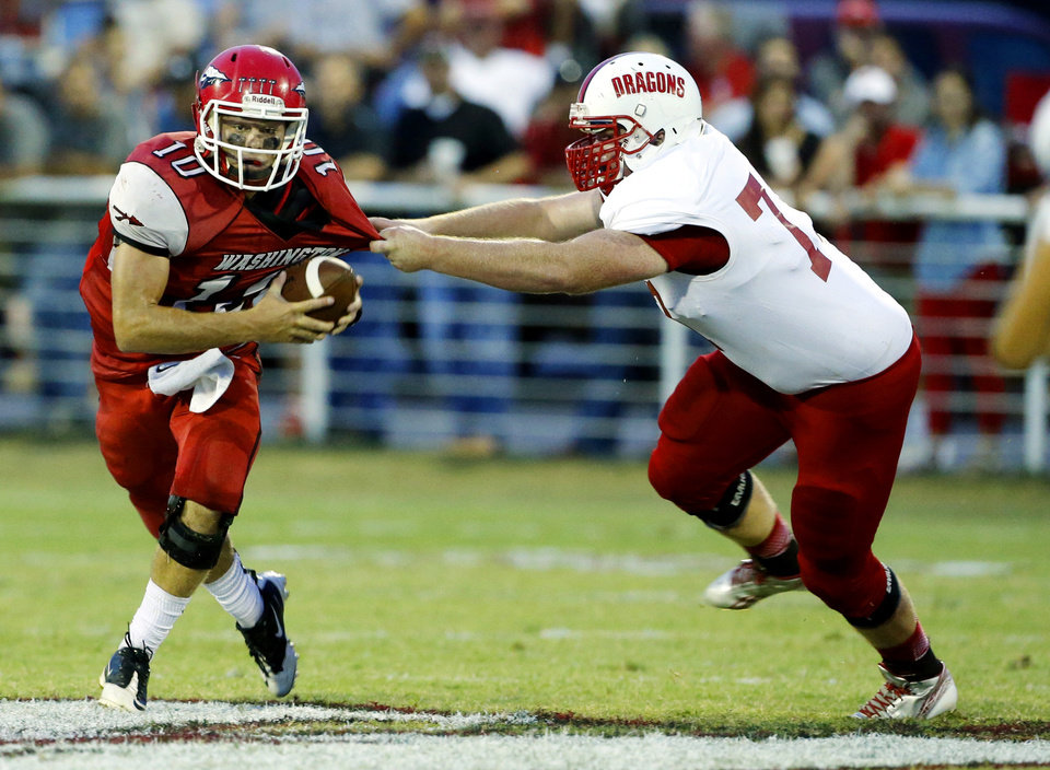Washington quarterback Brock Harmon tries to slip the tackle by Purcell's Colby Lindsey in high school football on Friday, Sept. 13, 2013 in Washington, Okla.  Photo by Steve Sisney, The Oklahoman