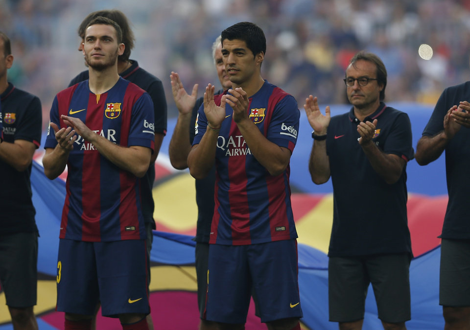 Photo - Barcelona's Luis Suarez, from Uruguay, centre, reacts during the official presentation of the Barcelona F.C team for the season 2014-2015 ahead of the Joan Gamper trophy match at the Camp Nou in Barcelona, Spain, Monday, Aug. 18, 2014. (AP Photo/Emilio Morenatti)