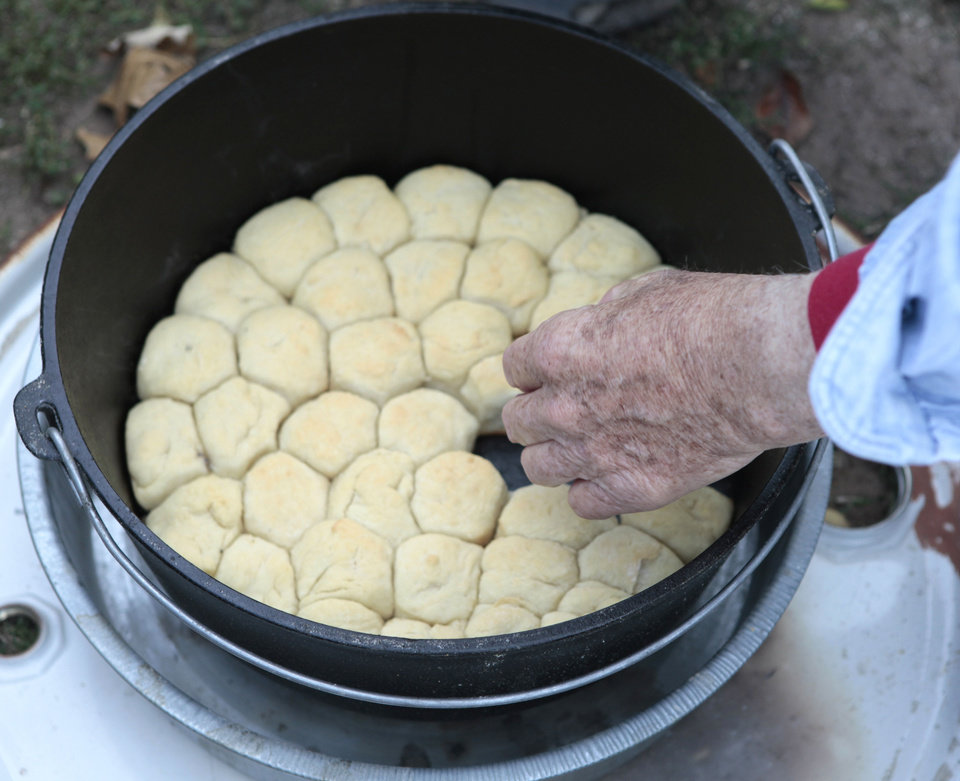 Photo - Lynn Shackelford with the Oklahoma History Center checks the biscuits he is cooking at Lincoln Elementary School in Norman.  Photo By David McDaniel, The Oklahoman  David McDaniel - The Oklahoman
