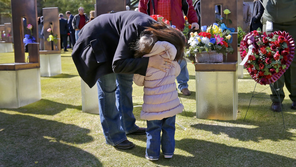 Dawn DeArmon hugs her grand daughter Madison Leinen as they stand in front of the chair of DeArmon\'s mother Kathy Cagle Leinen during the 18th Anniversary Remembrance Ceremony of the Oklahoma City bombing on Friday, April 19, 2013, in Oklahoma City, Okla. Photo by Chris Landsberger, The Oklahoman