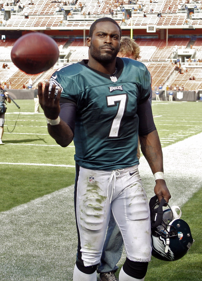 Photo -   Philadelphia Eagles quarterback Michael Vick tosses a ball to a fan after a 17-16 win over the Cleveland Browns in an NFL football game on Sunday, Sept. 9, 2012, in Cleveland. (AP Photo/Ron Schwane)