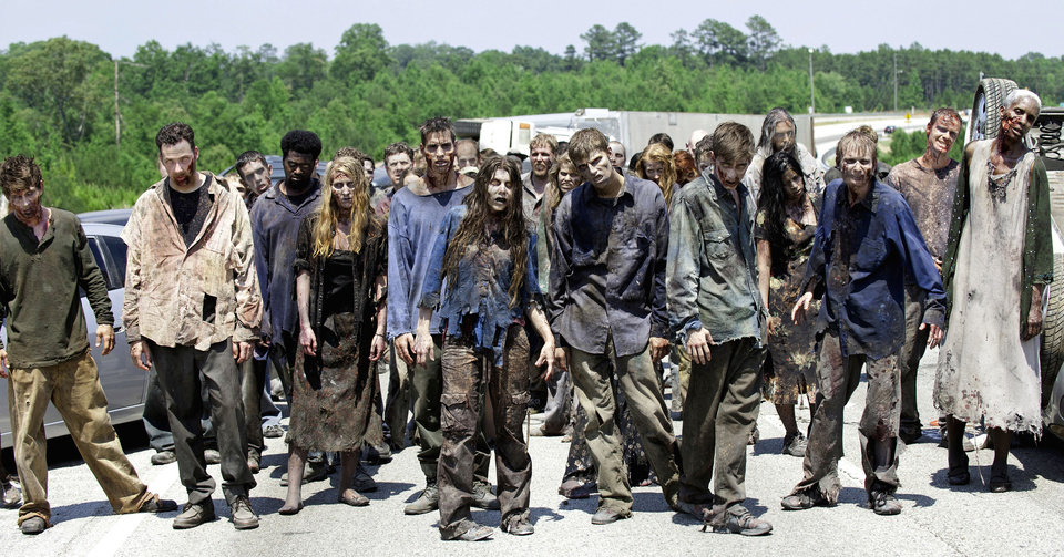 """Photo - FILE - In this image released by AMC, zombies appear in a scene from the second season of the AMC original series, """"The Walking Dead,"""" in Senoia, Ga. The seriesÂ' fourth season premieres on Oct. 13. Crews have been filming the new episodes in Georgia, but they keep locations of future episodes closely-guarded secrets until the shows air.  In Grantville, Ga., the townÂ's ruins were featured prominently last season.   In nearby Senoia, many scenes are filmed in the historic downtown area, transforming into the fictional town of Woodbury for the show.  (AP Photo/AMC, Gene Page)  NO SALES  ORG XMIT: GADG301"""
