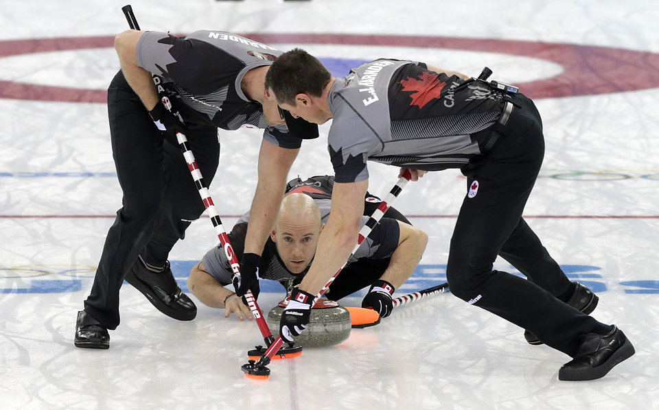 Photo - Canada's Ryan Fry, center, delivers the rock while teammates Ryan Harnden, left, and E.J. Harnden, right, sweep the ice during the men's curling gold medal game against Britain at the 2014 Winter Olympics, Friday, Feb. 21, 2014, in Sochi, Russia. (AP Photo/Wong Maye-E)