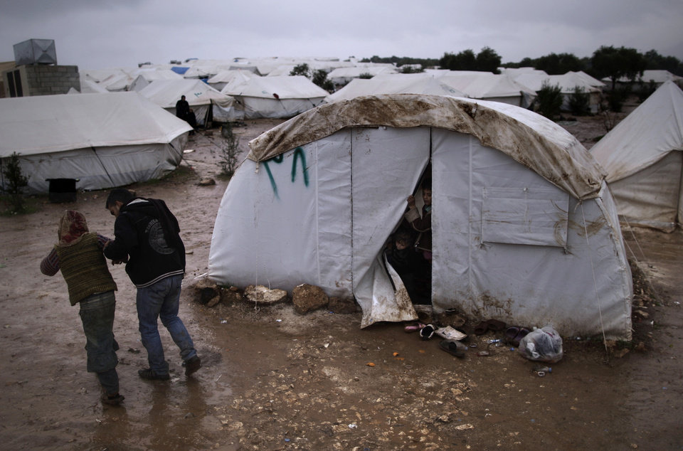 Photo - Children, who fled their home with their family, peek from their tent at a man helping a girl, after she fell on slippery ground, at a camp for displaced Syrians, in the village of Atmeh, Syria, Tuesday, Dec. 18, 2012. (AP Photo/Muhammed Muheisen)