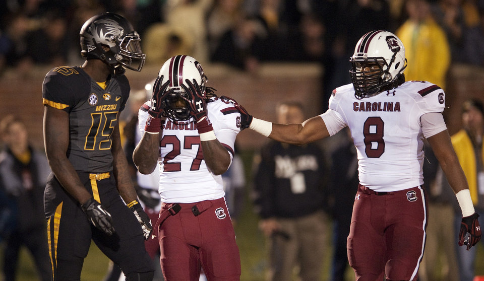 Photo - South Carolina's Kaiwan Lewis, right, consoles teammate Victor Hampton, center, as Missouri wide receiver Dorial Green-Beckham, left, walks by after Hampton nearly had an interception during the third quarter of an NCAA college football game Saturday, Oct. 26, 2013, in Columbia, Mo. (AP Photo/L.G. Patterson)