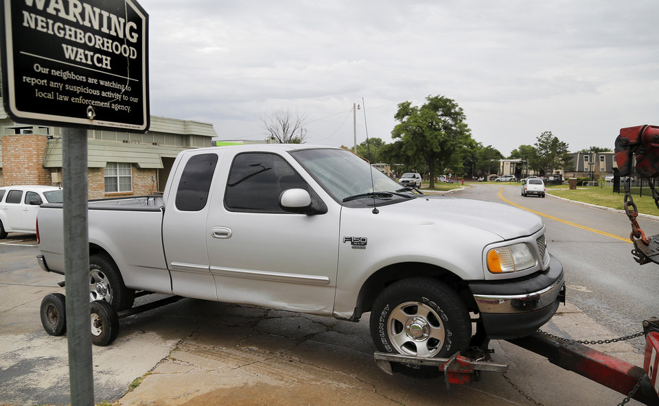 Photo - The truck in which two people were shot Wednesday is removed from a Northwest Oklahoma City apartment complex.  Photo by Jim Beckel, The Oklahoman  Jim Beckel