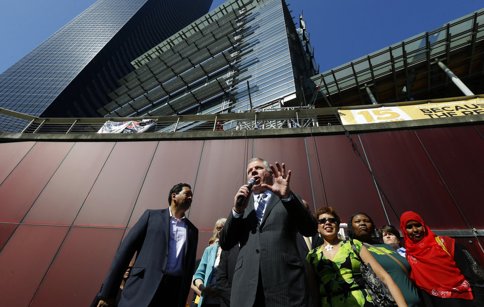 Photo - Seattle Mayor Ed Murray, center speaks Monday, June 2, 2014, at a rally outside Seattle City Hall after the Seattle City Council passed a $15 minimum wage measure. (AP Photo/Ted S. Warren)