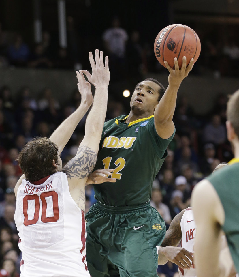 Photo - North Dakota State's Lawrence Alexander (12) shoots over Oklahoma's Ryan Spangler in the second half of a second-round game of the NCAA men's college basketball tournament in Spokane, Wash., Thursday, March 20, 2014. North Dakota State won in overtime, 80-75. (AP Photo/Elaine Thompson)