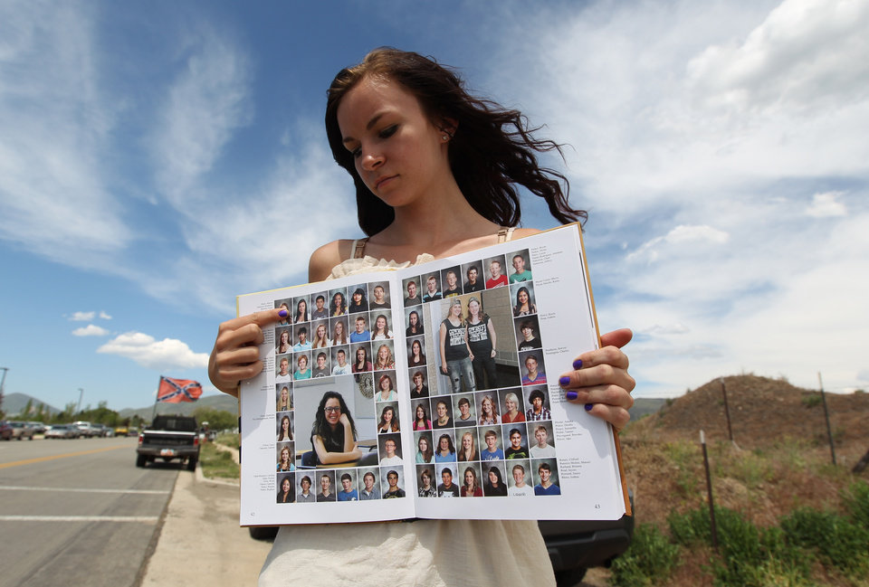 Photo - Wasatch High School sophomore Kimberly Montoya, 16, points to her altered school yearbook photo, upper left, Thursday, May 29, 2014, in Heber City, in Utah. A group of Utah high school students, including Montoya, said they were shocked and upset to discover their school yearbook photos were digitally altered, with sleeves and higher necklines drawn on to cover up bare skin.  (AP Photo/Rick Bowmer)