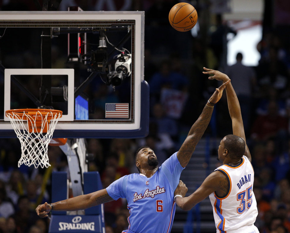 Photo - Oklahoma City 's Kevin Durant (35) shoots over Los Angeles' DeAndre Jordan (6) during the NBA game between the Oklahoma City Thunder and the Los  Angeles Clippers at the Chesapeake Energy Arena, Sunday, Feb. 23, 2014. Photo by Sarah Phipps, The Oklahoman