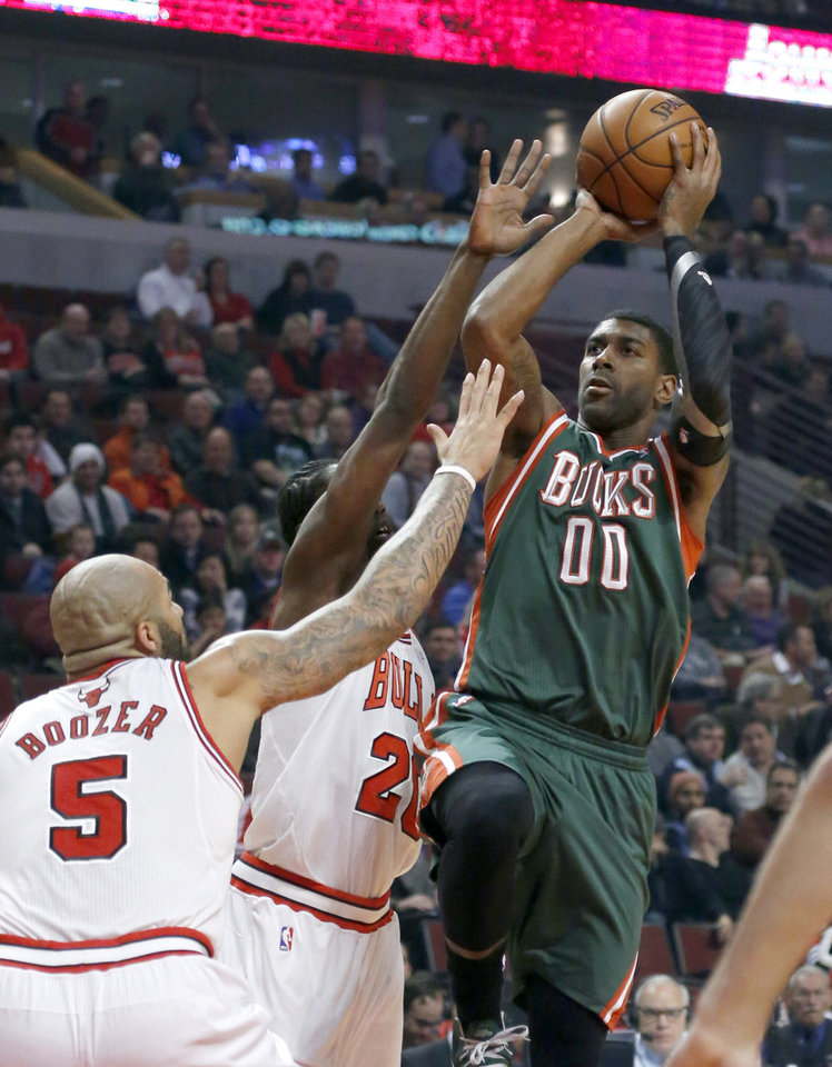 Photo - Milwaukee Bucks shooting guard O.J. Mayo (00) shoots over Chicago Bulls forward Carlos Boozer (5) and Tony Snell during the first half of an NBA basketball game Tuesday, Dec. 10, 2013, in Chicago. (AP Photo/Charles Rex Arbogast)